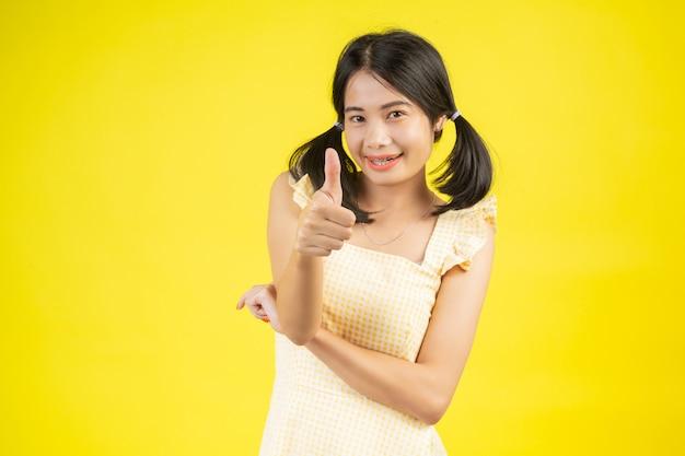 Een mooie vrouw die blij is met verschillende gebaren op een geel. Gratis Foto