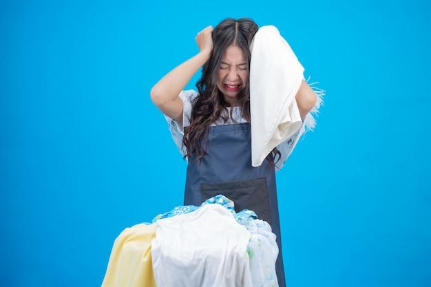 Een mooie vrouw die een doek houdt bereid om op blauw te wassen Gratis Foto