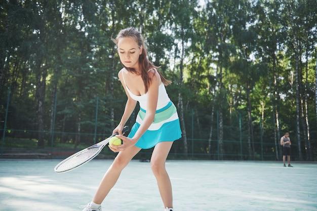 Een mooie vrouw die een tennisbaan in sportkleding draagt op de baan. Gratis Foto