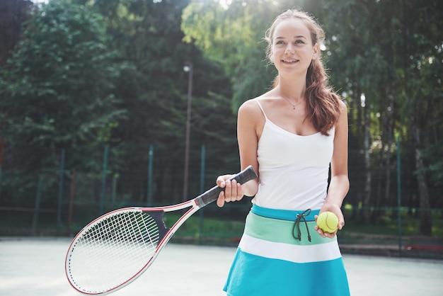 Een mooie vrouw die een tennisbal van sportkleding draagt. Gratis Foto