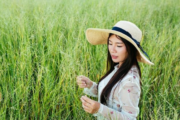 Een mooie vrouw die gelukkig in het grasland zit. Gratis Foto