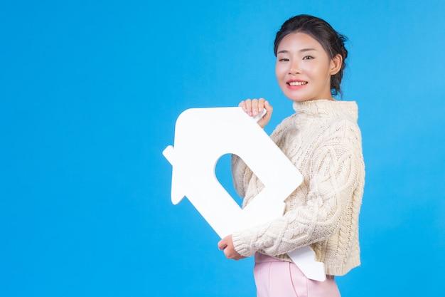Een mooie vrouw, gekleed in een nieuw wit shirt met lange mouwen en een huissymbool. huizenhandel. Gratis Foto