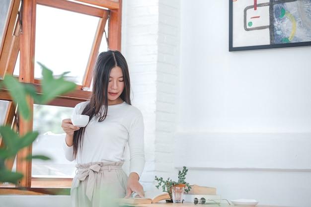 Een mooie vrouw, gekleed in een wit shirt met lange mouwen in een koffieshop Gratis Foto