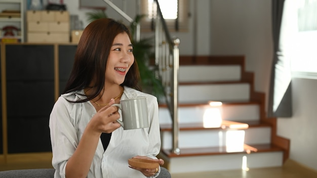 Een mooie vrouw houdt thuis een kopje koffie en glimlacht Premium Foto