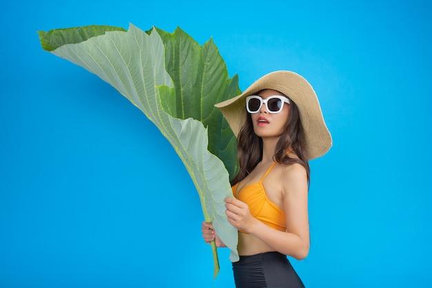 Een mooie vrouw in een zwempak met een groen blad vormt op blauw Gratis Foto