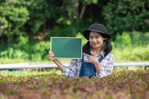 Een mooie vrouw met een groen bord in een gewassen kwekerij. Gratis Foto