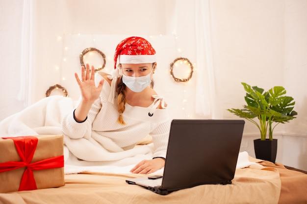 Een mooie vrouw met een masker en een kerstmuts feliciteert haar vrienden online via een videogesprek Premium Foto