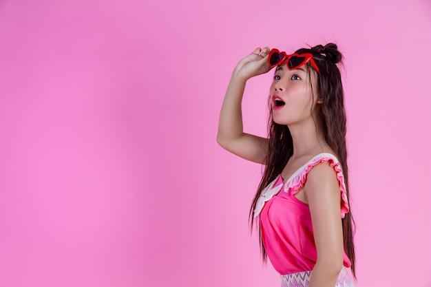 Een mooie vrouw met rode bril met een grote hoed op een roze. Gratis Foto