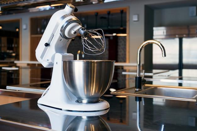 Een mooie witte mixer met een metalen kop Premium Foto
