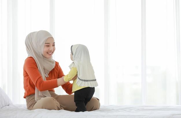 Een moslimmoeder en peuter zijn binnen in hun slaapkamer. de moeder draagt een hoofddoek Premium Foto
