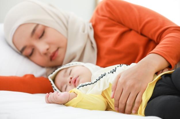 Een moslimvrouw met een hoofddoek ligt in een slaapkamer met haar peuter. Premium Foto