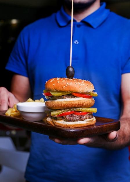 Een ober met een bord fastfood met hamburger en gebakken aardappelen. Gratis Foto