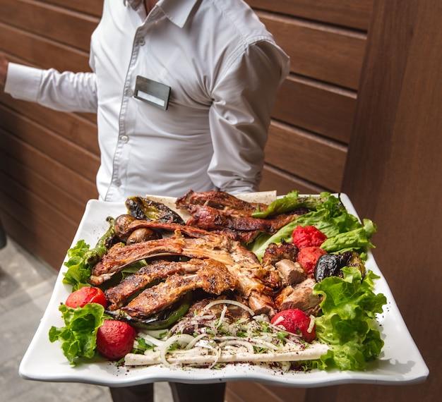 Een ober met een groot bord kebab kip in zijn hand Gratis Foto