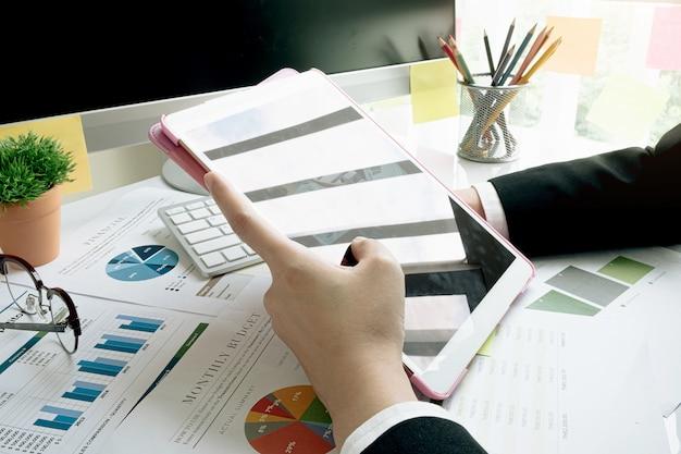 Een onderneemster die investeringsgrafieken analyseert op zijn werkplek en zijn laptop en aanraking ipad gebruikt. Premium Foto