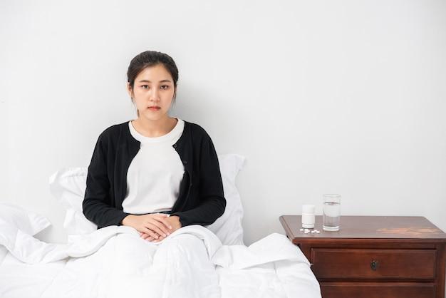 Een ongemakkelijke vrouw zit op het bed en heeft medicijnen op tafel. Gratis Foto