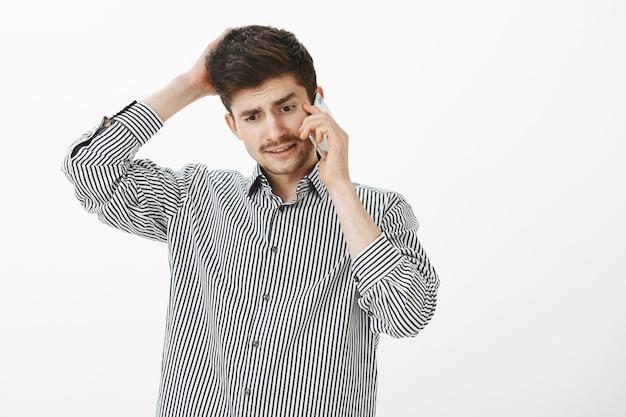 Een onrustige officemanager kan geen antwoord geven. portret van verwarde ondervraagde knappe mannelijke student met snor, achterhoofd krabben en praten over smartphone, naar beneden te kijken, excuses maken Gratis Foto