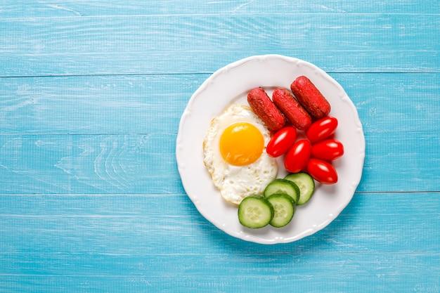 Een ontbijtbord met cocktailworstjes, gebakken eieren, cherrytomaatjes, snoep, fruit en een glas perziksap. Gratis Foto