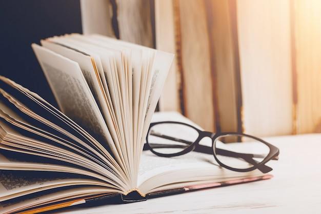 Een open boek met een bril op een houten tafel tegen de achtergrond van een aantal boeken, vintage toning. Premium Foto