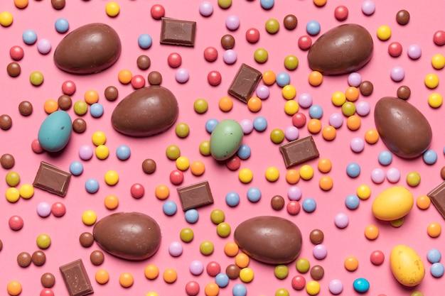 Een opgeheven mening van gemsuikergoed en chocoladepaaseieren op roze achtergrond Gratis Foto