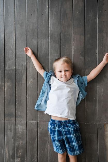 Een opgeheven mening van jongen die op houten vloer ligt Gratis Foto