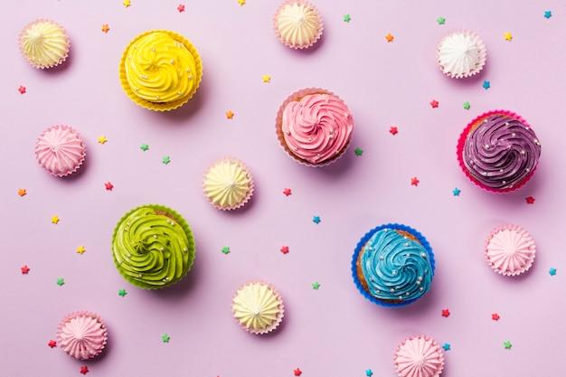 Een opgeheven mening van kleurrijke ster bestrooit; aalaw en muffins op roze achtergrond Gratis Foto