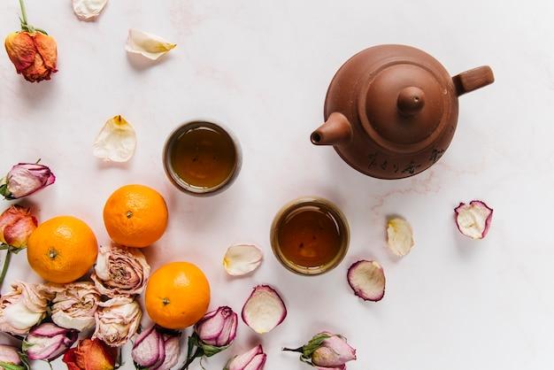 Een oranje en droge roos met kruidenthee in kleitheepot en theekopjes Gratis Foto
