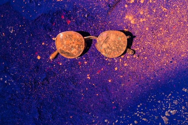 Een oranje holi-kleur over de zonnebril op blauw poeder Gratis Foto