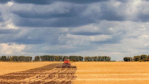 Een oranje moderne tractor ploegt de aarde in een gouden veld van tarwe op een zomerse dag, in de lucht een stapelwolk Premium Foto