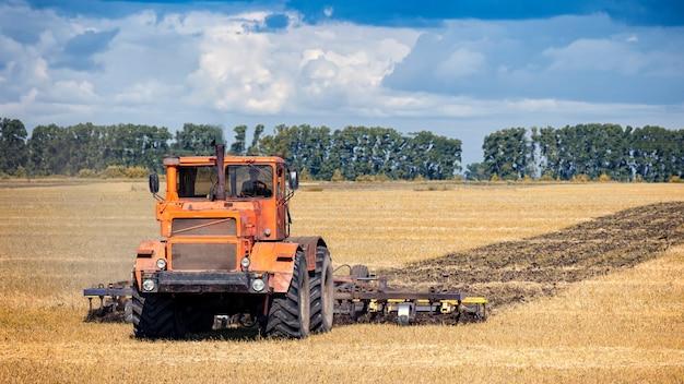 Een oranje moderne tractor ploegt het gouden aardeveld van tarwe Premium Foto