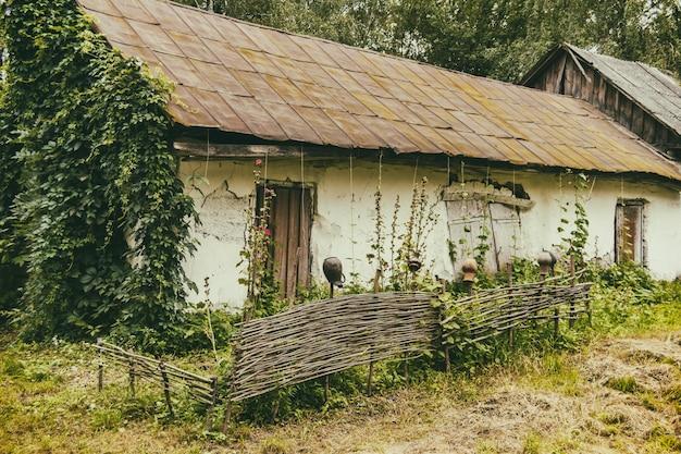 Een oud huis met een omheining in een arm dorp. vernietigd gebouw. zomer Premium Foto