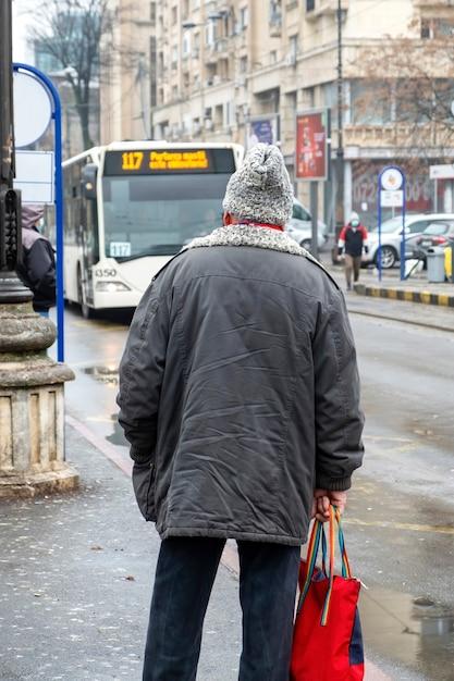 Een oude man in een jasje en een hoed gemaakt van wol op een halte, straat op de achtergrond, bewolkt weer in boekarest, roemenië Gratis Foto