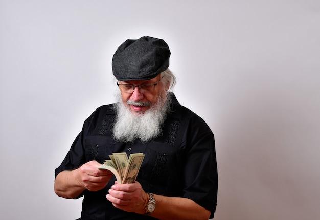 Een oude man met een baard die zijn geld telt Gratis Foto