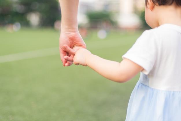 Een ouder houdt de hand van een klein kind vast Premium Foto