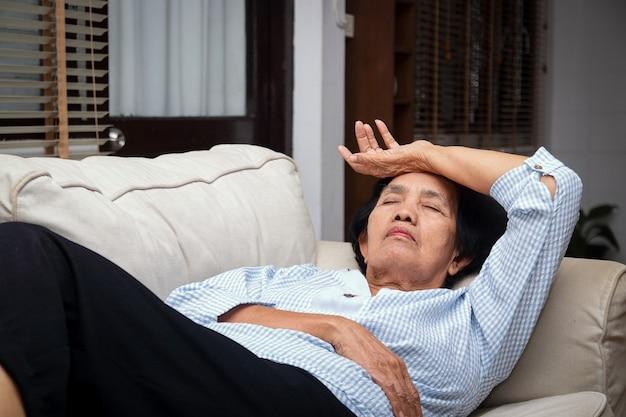 Een oudere aziatische vrouw ligt thuis gestrest op de bank Premium Foto