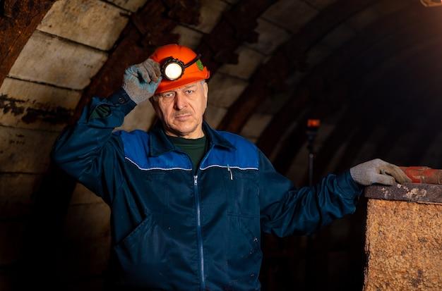 Een oudere man, gekleed in werkoverall en een helm, staat bij de oude caravan. Premium Foto