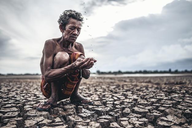Een oudere man zit in contact met regen in het droge seizoen, opwarming van de aarde, selectie focus Gratis Foto