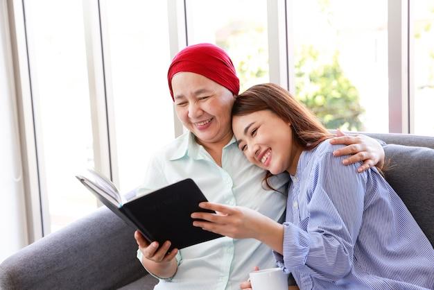 Een oudere vrouw met kanker die een hoofddoek draagt, ontspant thuis met haar volwassen dochter en leest lachend een boek. de vrouwen zijn vol hoop voor de toekomst. Premium Foto