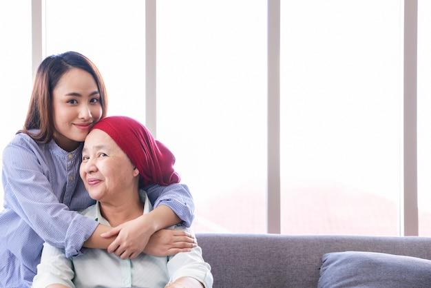 Een oudere vrouw met kanker ontspant thuis met haar volwassen dochter. de vrouwen hebben hoop voor de toekomst. Premium Foto