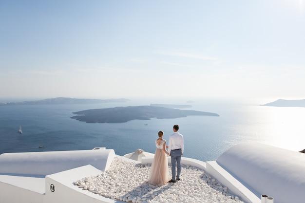 Een paar pas getrouwde mensen in prachtige kledij genieten van hun huwelijksreis in griekenland Premium Foto