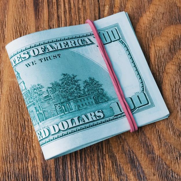 Een pak dollars gebonden met een elastische band ligt op houten planken. Premium Foto