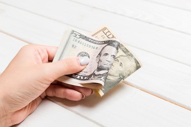Een pak van vijf en tien dollarbiljetten in vrouwelijke hand Premium Foto