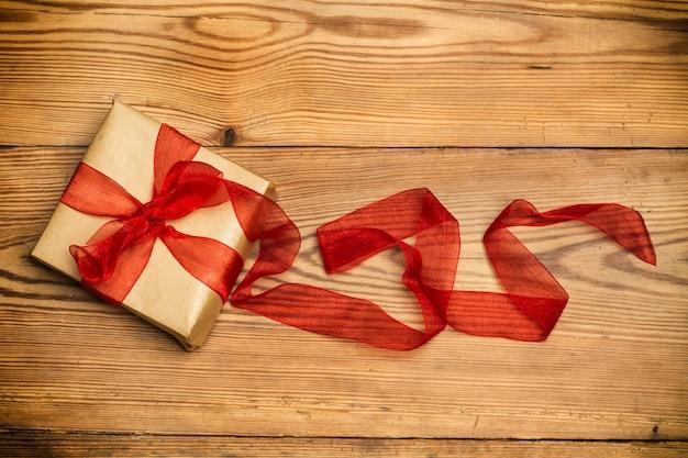 Een pakket met een rode strik op een houten tafel in bovenaanzicht Premium Foto