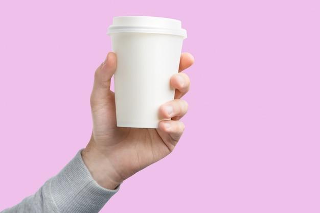 Een papieren kopje koffie in de hand. witboek ter beschikking geïsoleerde kop van koffie Premium Foto