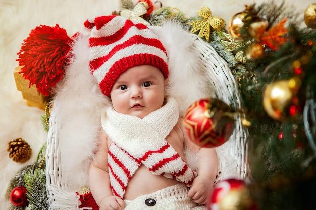 Een pasgeboren baby onder een kerstboom Premium Foto