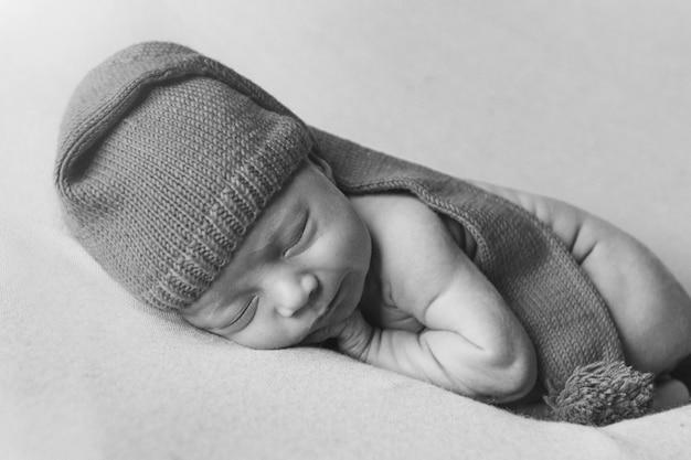 Een pasgeboren baby slaapt in een kerstmuts op een wit. een gezonde levensstijl, ivf, kerstmis, nieuwjaarsvakantie, speelgoed Premium Foto