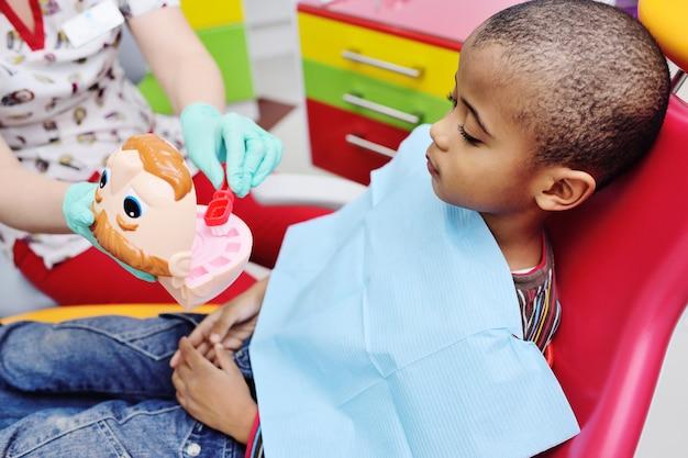 Een pediatrische tandarts leert een afrikaans amerikaans kind dat in een tandartsstoel zit om zijn tanden goed te poetsen. Premium Foto