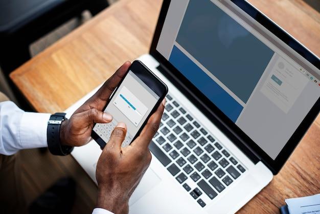 Een persoon die een mobiele telefoon en een laptop gebruikt Premium Foto