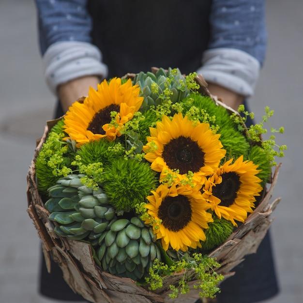 Een persoon die een rustiek boeket met zonnebloemen en suculenten aanbiedt Gratis Foto