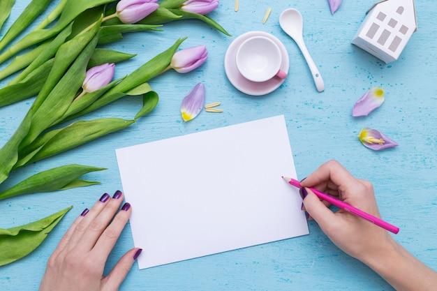 Een persoon die op wit papier tekent met een roze potlood in de buurt van paarse tulpen en een koffiekopje Gratis Foto