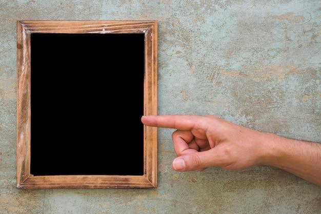Een persoon die vinger op houten leeg frame over de grungeachtergrond richt Gratis Foto